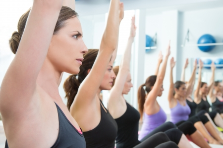 aerobics class: Aerobic Pilates personal trainer in a gym group class in a row