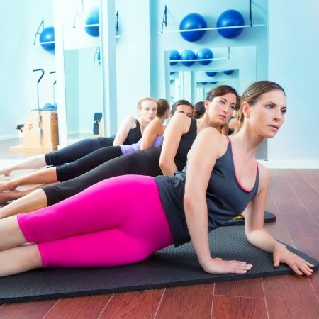 Matte: Pilates Frauengruppe liegend auf Matte mit Turnlehrer an der Vorderseite