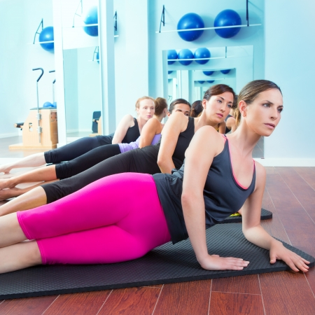 Pilates women group lying on mat with gym instructor on the front photo