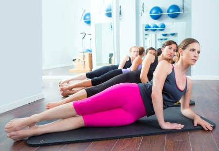 Pilates women group lying on mat with gym instructor on the front