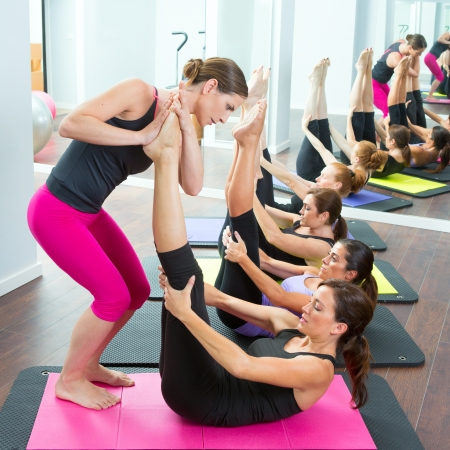 aerobics: Aerobics Pilates personal trainer helping women group in a gym class