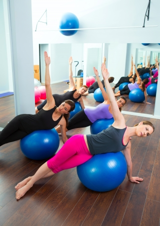 Aerobic Pilates women group with stability ball in a row on mirror gym photo
