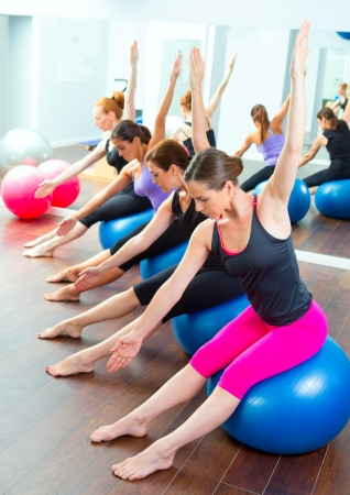 limber: Aerobic Pilates women group with stability ball in a row on mirror gym