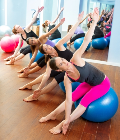 Pilates aerobics women group with stability ball in a row on mirror gym photo