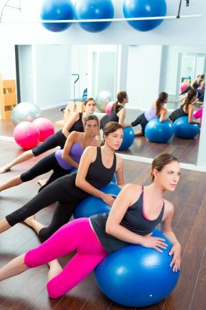 pilate: A�robic Pilates groupe de femmes avec boule de stabilit� dans une rang�e sur miroir salle de gym