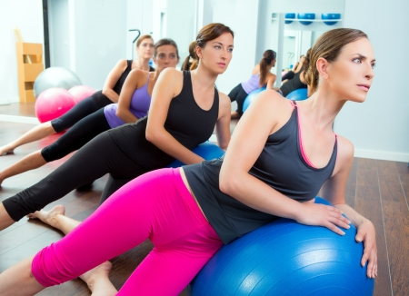 stability: Aerobic Pilates women group with stability ball in a row on mirror gym