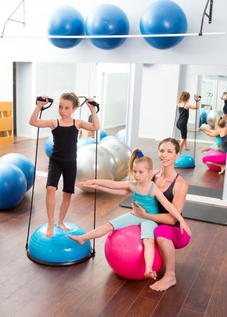 Aerobics woman personal trainer of children girl with stability ball photo