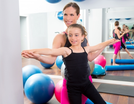 limber: Aerobics woman personal trainer of children girl stability with foam roller