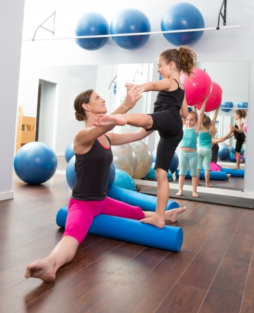 Aerobics woman personal trainer of children girl stability with foam roller Stock Photo - 15429317