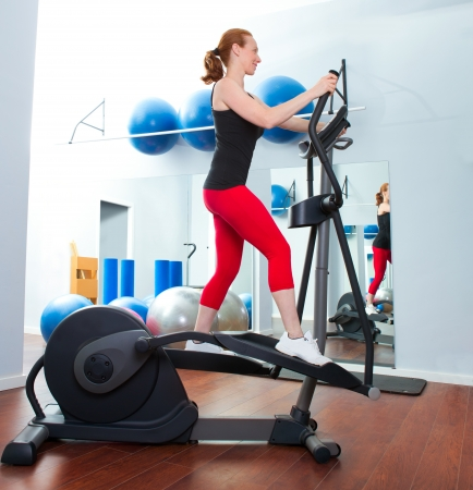 Aerobics cardio training woman on elliptic crosstrainer bicycle at gym photo