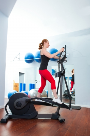 Aerobics cardio training woman on elliptic crosstrainer bicycle at gym Stock Photo - 20130181