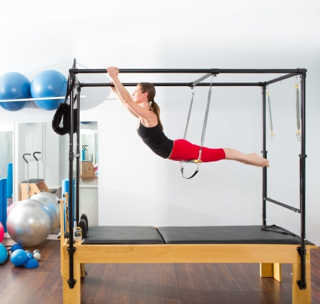 trapeze: Aerobics pilates instructor woman in cadillac fitness exercise