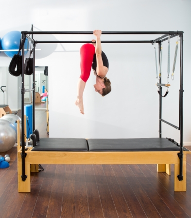 trapeze: Pilates aerobic instructor woman in cadillac fitness exercise