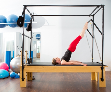 gymnastics equipment: Aerobics pilates instructor woman in cadillac fitness exercise