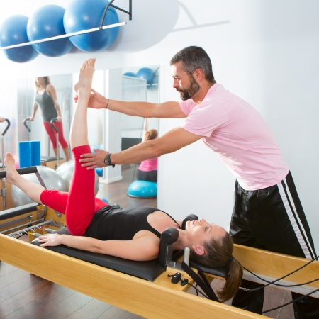 Pilates aerobic personal trainer instructor man in cadillac fitness woman exercise Stock Photo - 15444281