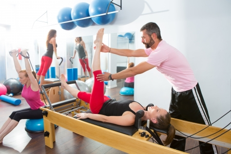 instructeur: Pilates aerobics personal trainer instructeur man in cadillac fitness vrouw oefening