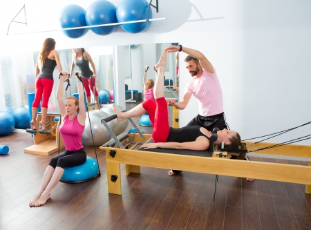 Pilates aerobic personal trainer instructor man in cadillac fitness woman exercise Stock Photo - 15444256