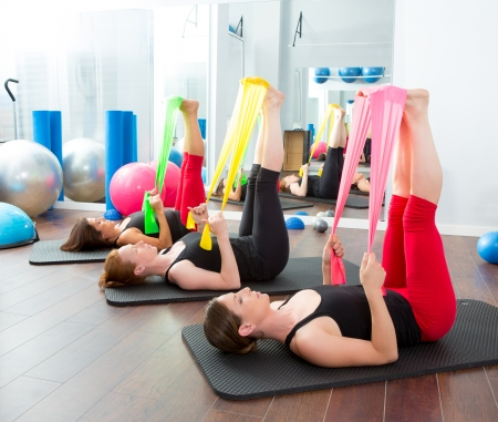 aerobic training: Aerobics pilates women group with rubber bands in a row at fitness gym Stock Photo