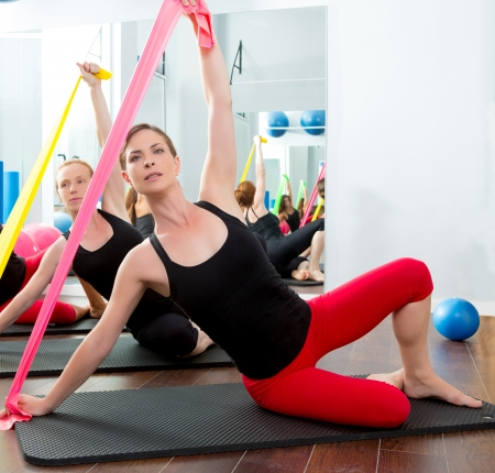 rubber bands: Aerobics pilates women group with rubber bands in a row at fitness gym Stock Photo
