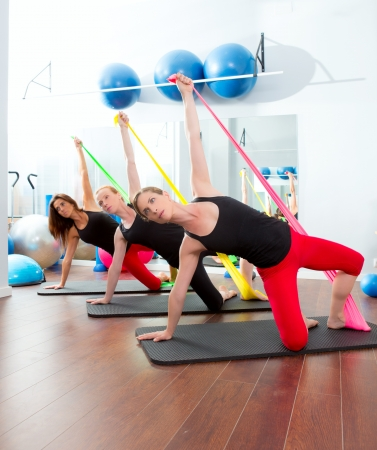 Aerobics pilates women group with rubber bands in a row at fitness gym photo