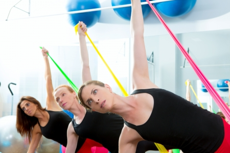 limber: Aerobics pilates women group with rubber bands in a row at fitness gym Stock Photo