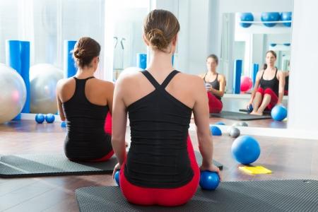 toning: Pilates toning ball in women fitness class rear mirror view
