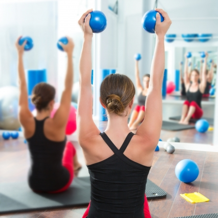 back training: Pilates toning ball in women fitness class rear mirror view