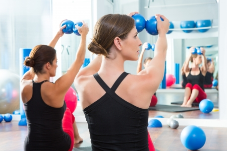 limber: Pilates toning ball in women fitness class rear mirror view