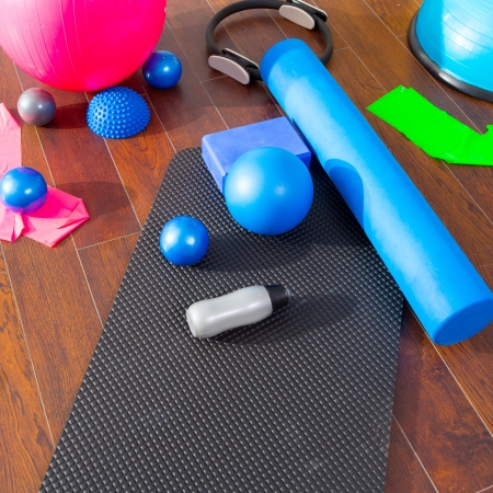 body toning: Aerobic Pilates stuff like mat balls roller magic ring rubber bands on wooden floor