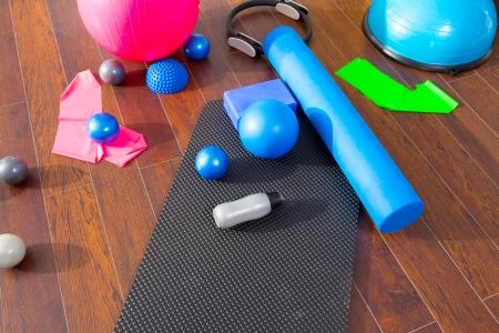 body toning: Aerobic Pilates stuff like mat balls roller magic ring rubber bands on wooden floor