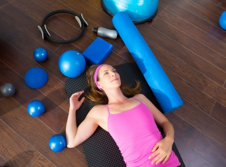 Aerobics instructor woman tired resting lying on mat with pilates balls and bands photo