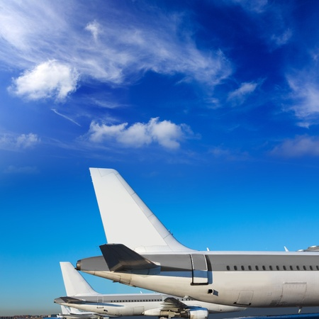 airport runway: Airplanes in a row under blue sunny sky Stock Photo