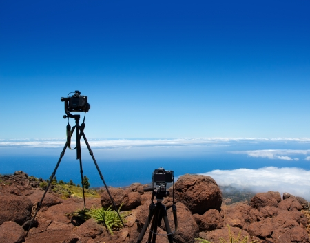 Landscape photographer tripods and cameras over high mountain over clouds photo