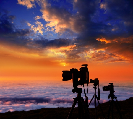 camera tripods of nature photographer work in high mountain sunset over sea of clouds Stock fotó