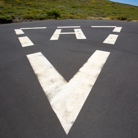 heliport: heliport triangle white soil painted sign in pavement