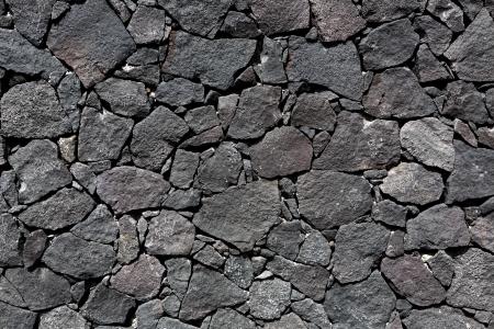 Black lava stone volcanic masonry wall in Canary Islands photo
