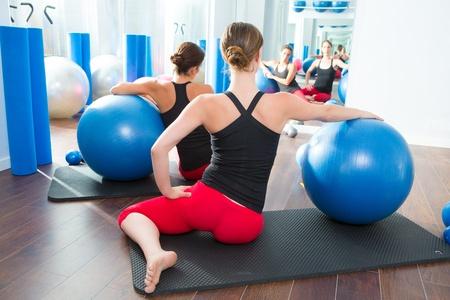 toning: Blue stability ball in women Pilates class rear mirror view