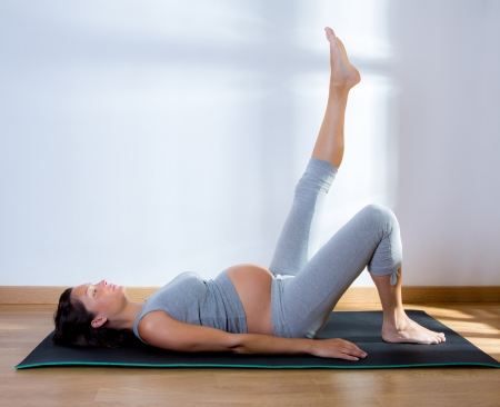 pregnant exercise: Beautiful pregnant woman at gym fitness exercise practicing aerobics on mat Stock Photo