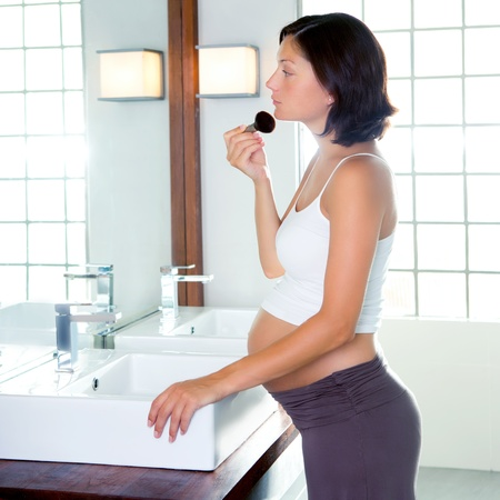 brush in: Beautiful pregnant woman on modern bathroom makeup with brush in mirror