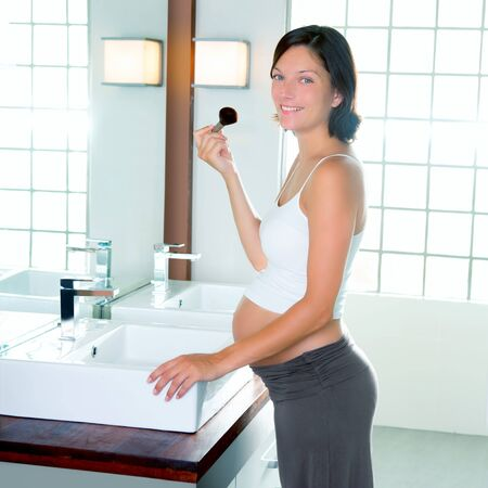 Beautiful pregnant woman on modern bathroom makeup with brush in mirror photo
