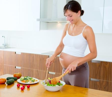 enceinte: Beautiful pregnant woman at home kitchen preparing salad