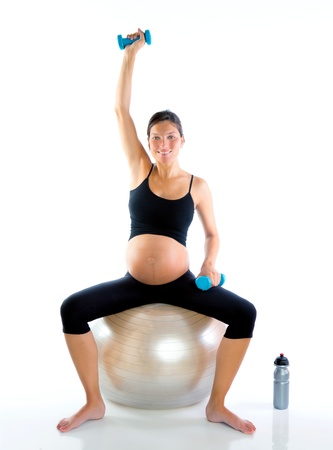 pregnant exercise: Beautiful pregnant woman at fitness gym with dumbells on aerobics ball
