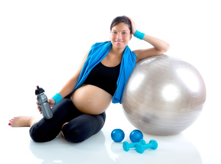enceinte: Beautiful pregnant woman at fitness gym relaxed with aerobics ball