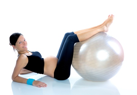 Beautiful pregnant woman at fitness gym with on aerobics ball photo