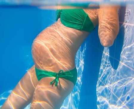 happy pregnant: Hermosa mujer embarazada relajado bajo el agua azul de la piscina