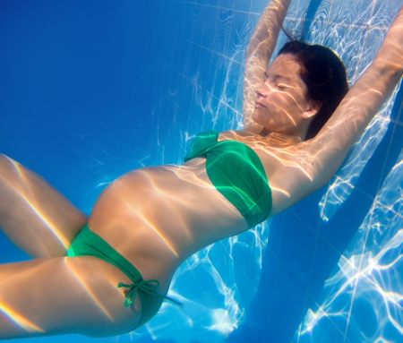 underwater woman: Beautiful pregnant woman underwater blue pool relaxed