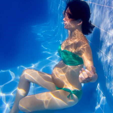 swimming to float: Beautiful pregnant woman underwater blue pool relaxed