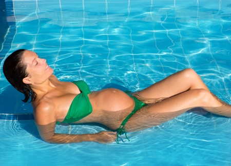 Beautiful pregnant woman sun tanning relaxed at blue pool with green bikini Stock Photo - 15599941
