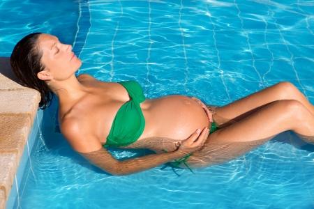 happy pregnant: Sol hermoso bronceado mujer embarazada relajado en la piscina azul con bikini verde