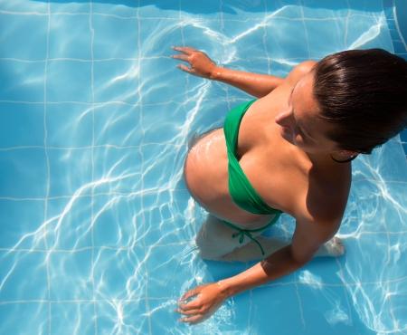 mujeres embarazadas: Sol hermoso bronceado mujer embarazada relajado en la piscina azul con bikini verde